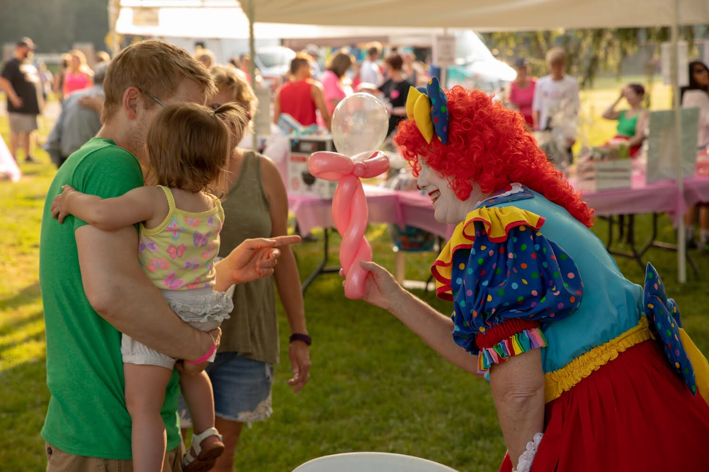 clown showing child balloon